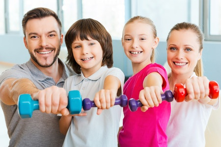 37824011 - living a healthy life together. happy family holding different sports equipment while standing close to each other in health club